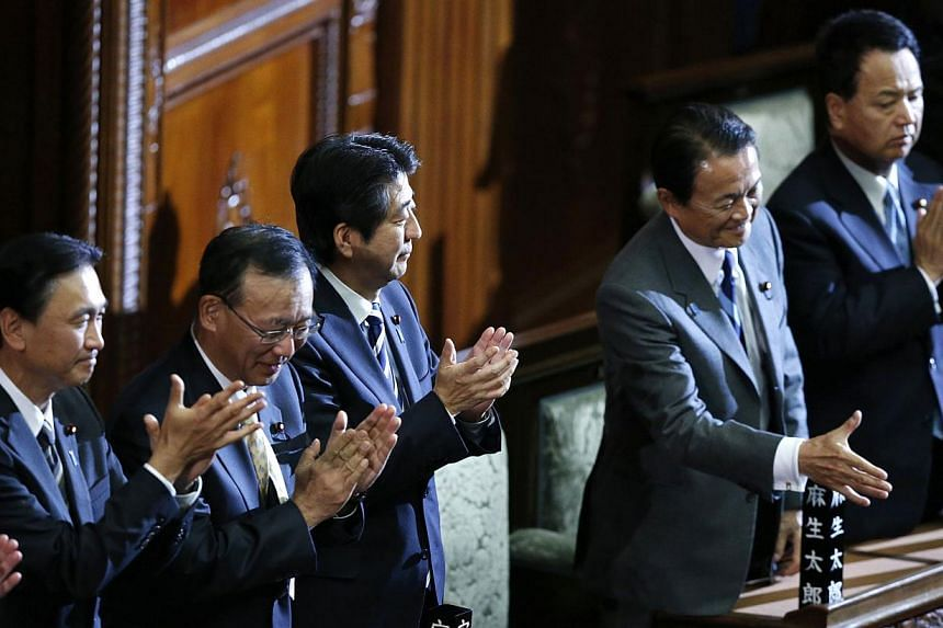 Japan's Prime Minister Shinzo Abe (third from left) and his cabinet ministers clap their hands after the government proposed state secrecy act was passed at the Lower House during the plenary session of the parliament in Tokyo on Tuesday, Nov 26, 201