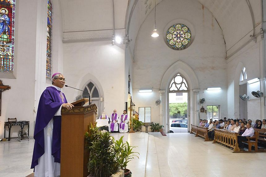 Archbishop William Goh holds his first mass for Typhoon Haiyan victims at the Church of Saints Peter and Paul on Tuesday, Nov 26, 2013. -- ST PHOTO: ASHLEIGH SIM