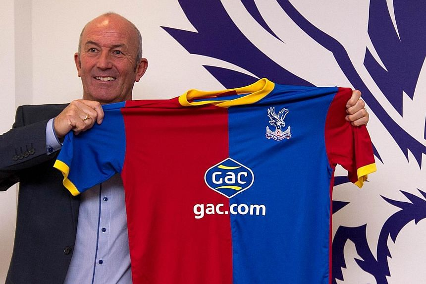 Crystal Palace's welsh football manager Tony Pulis poses for photographers with a team shirt after being unveiled as the club's new manager in south London on Nov 25, 2013. Pulis is relishing the task of trying to maintain his proud 21-year record of