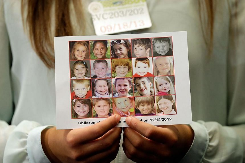 Ms Kyra Murray holds a photo with victims of the shooting at Sandy Hook Elementary School during a press conference at the United States Capitol calling for gun reform legislation and marking the nine-month anniversary of the shooting on Sept 18, 201
