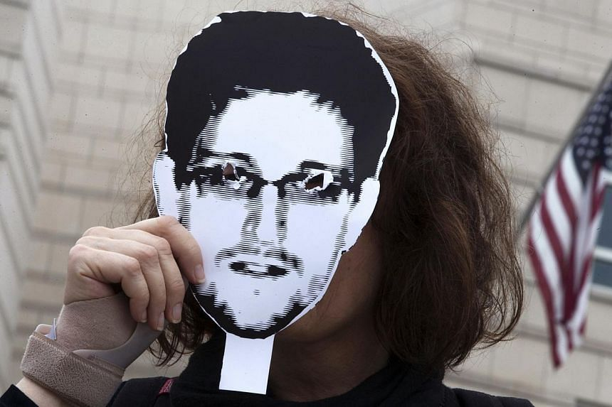 A woman holds a portrait of former U.S. spy agency contractor Edward Snowden in front of her face as she stands in front of the U.S. embassy during a protest in Berlin, in this file photo from July 4, 2013. British and United States (US) intelli