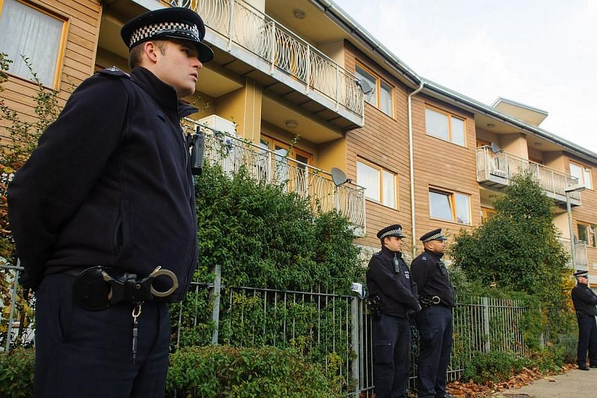 Police officers stand outside flats as police conduct house-to-house inquires in the area where three women were rescued in south London, on Saturday, Nov 23, 2013. The youngest of the three women held as 'slaves' for 30 years in London bombarde