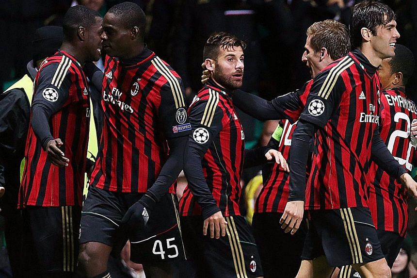 AC Milan players celebrate after their Colombian defender Cristian Zapata scored their second goal during the UEFA Champions League group H football match between Celtic and AC Milan at Celtic Park in Glasgow on November 26, 2013. AC Milan kept