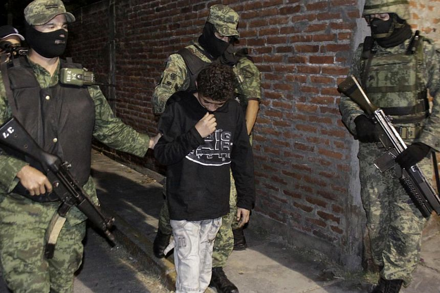 "In this Dec. 3, 2010 file photo, Mexican soldiers present Edgar ""El Ponchis"" Jimenez Lugo to the media in the city of Cuernavaca, Mexico. Mexican authorities on Tuesday released the US-born teenager who was convicted at age 14 for working as a hitman"