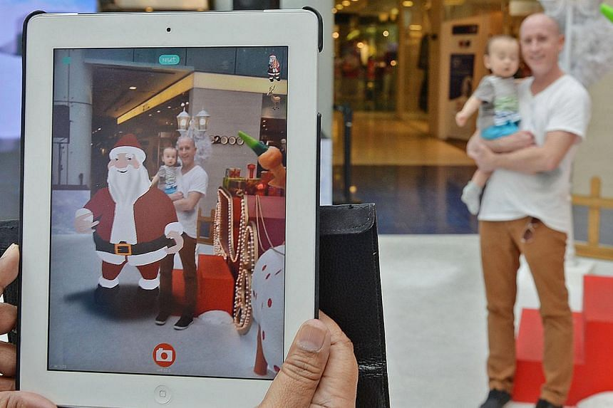 Marina Square shopper Nick Francis Stephens, 39, and his 11-month-old daughter Kai getting their photo taken with a virtual Santa in the image, at the mall's Augmented Reality winter wonderland display. -- ST PHOTO: RAJ NADARAJAN