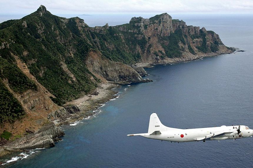 Japan Maritime Self-Defence Force's P-3C Orion surveillance plane flies over the disputed islands in the East China Sea, called the Senkaku in Japan and Diaoyu in China on Thursday, Oct 13, 2011. China insisted on Wednesday, Nov 27, 2013, i