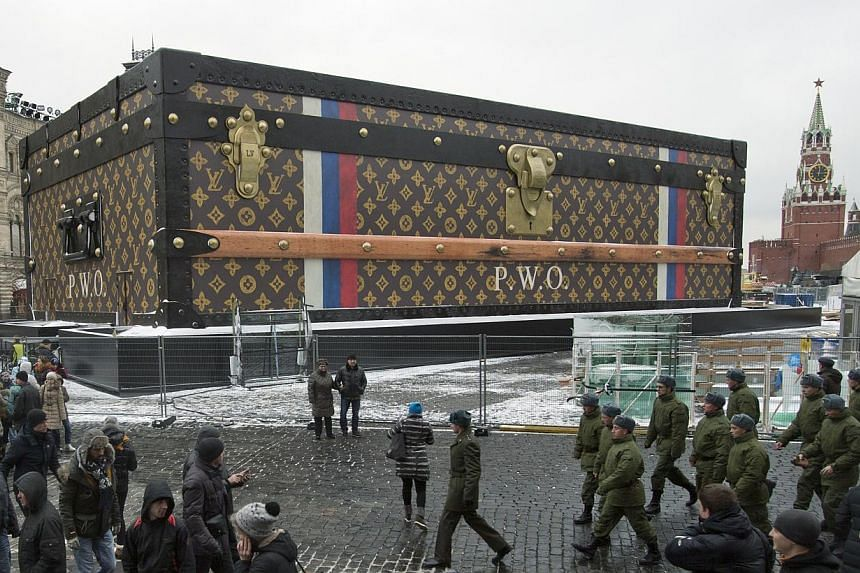 Tourists and visitors pass by a giant Louis Vuitton suitcase erected at the Red Square in Moscow, Russia on Wednesday, Nov 27, 2013. -- PHOTO: AP