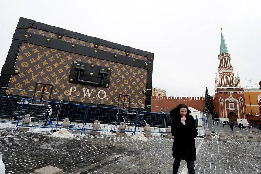 A woman walks in front of a giant Louis Vuitton trunk on Red Square in Moscow on Wednesday, Nov 27, 2013. -- PHOTO: AFP