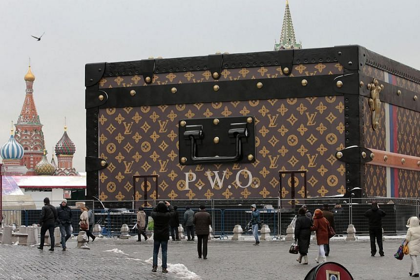 People walk past a Louis Vuitton pavilion which is in the shape of a giant suitcase in central Moscow on Wednesday, Nov 27, 2013. French luxury brand Louis Vuitton has been ordered to remove a giant trunk put up on Moscow's iconic Red Squar