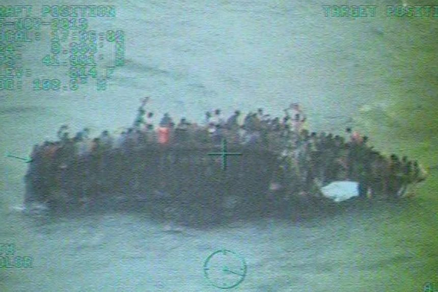 This image taken from video made available by the U.S. Coast Guard shows a group of Haitian migrants sitting on the hull of a capsized sailboat near Staniel Cay, Bahamas, on Tuesday, Nov 26, 2013. At least 10 Haitian migrants were killed and 110