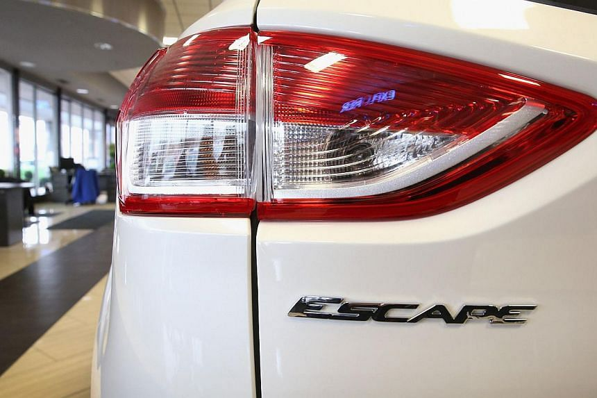 A 2014 Ford Escape sits in the showroom at a dealership on Nov 26, 2013 in Niles, Illinois. US auto giant Ford ordered a recall of nearly 150,000 of its popular Escape vehicle on Tuesday, citing a potential risk of engine fire. -- PHOTO: AFP