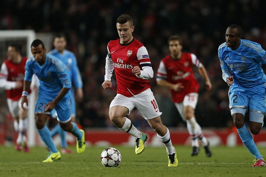 Arsenal's English midfielder Jack Wilshere (centre) runs with the ball as Marseille's Comorean defender Kassim Abdallah (right) follows during the UEFA Champions League group F football match between Arsenal and Olympique de Marseille at the Emirates
