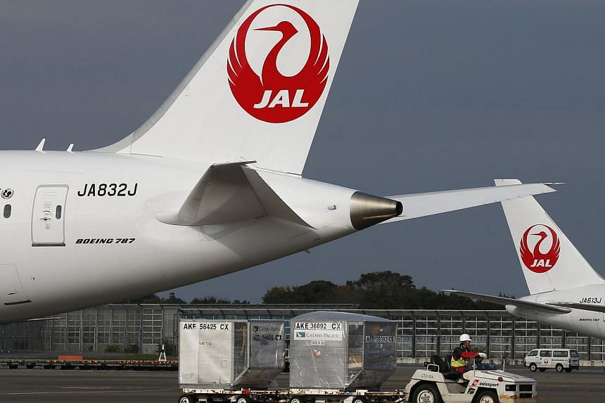 A airport worker drives a luggage transport vehicle past one of the company's Boeing Co's 787 Dreamliner plane (left) and a Beoing 767 at Narita international airport in Narita, east of Tokyo, on Nov 11, 2013. -- FILE PHOTO: REUTERS