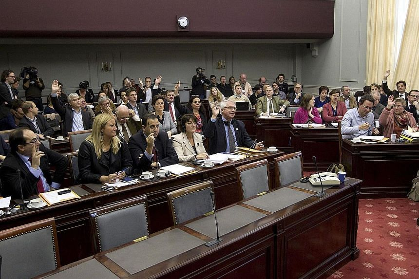 Belgium's Senate members vote during a session of the Senate's justice and social affairs commission on the expansion of the euthanasia law for minors, at the federal parliament in Brussels, on Wednesday, Nov 27, 2013. Belgium, one of only a few