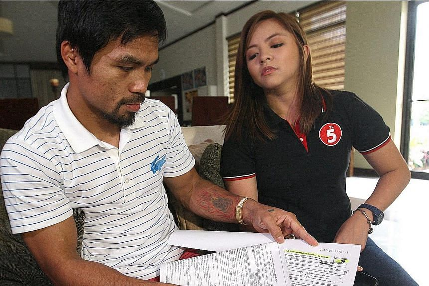 Filipino boxing icon Manny Pacquiao shows reporters US Internal Revenue Forms which he claims to have filed in 2008 and 2009, in General Santos, southern Philippines, on Wednesday, Nov 27, 2013. Philippines authorities, on Wednesday, Nov 27, 201