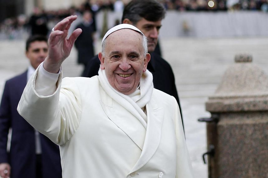 Pope Francis waves as he conducts his weekly general audience at St Peter's Square at the Vatican on Nov 27, 2013. Pope Francis took on the issue of high youth unemployment in his first interview aired exclusively in his home country of Argentina on