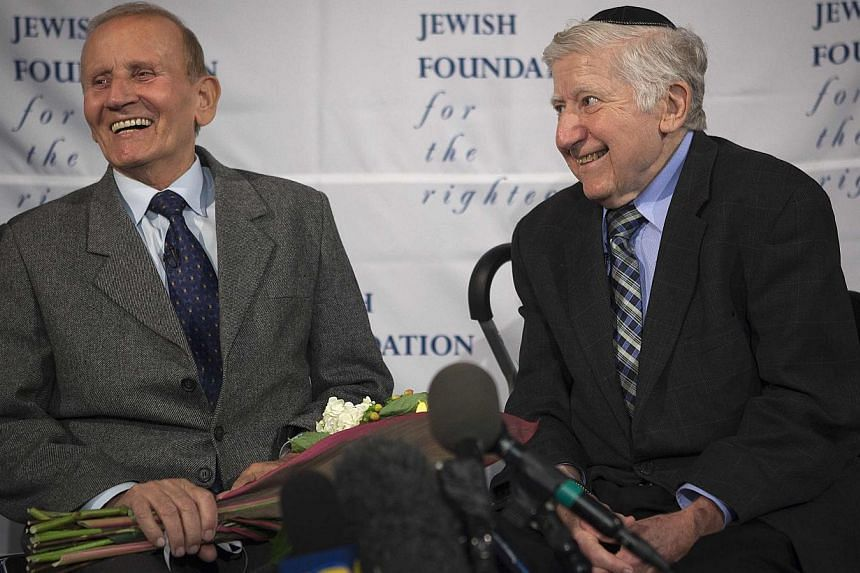 Holocaust survivor Mr Leon Gersten (right) and Mr Czelaw Polziec talk to the media at JFK airport in New York on Nov  27, 2013. A Jewish boy who hid from the Nazis in a haystack was reunited in New York after 70 years on Wednesday with the