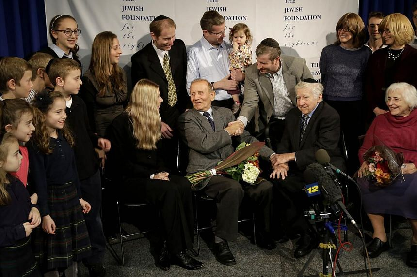 Mr Czeslaw Polziec, of Poland (centre) meets members of Mr Leon Gersten's family in New York, onNov 27, 2013. A Jewish boy who hid from the Nazis in a haystack was reunited in New York after 70 years on Wednesday with the Polish son whose paren