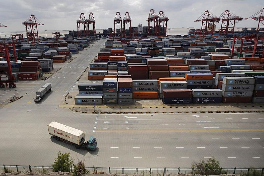 Container trucks drive past the container area at the Yangshan Deep Water Port, part of the newly announced Shanghai Free Trade Zone, south of Shanghai on Sept 26, 2013.China's new free-trade zone has drawn just 38 overseas firms in its first t