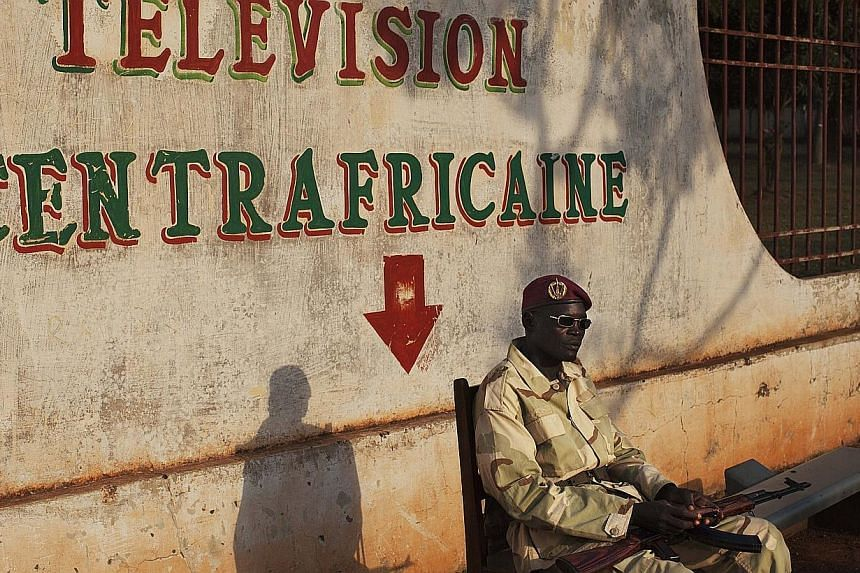 A Seleka soldier sits in front of the defunct national television headquarters in Bangui, Central African Republic, on Nov 27, 2013. The motley crew of fighters who overthrew the Central African Republic's government in March are raging beyond their