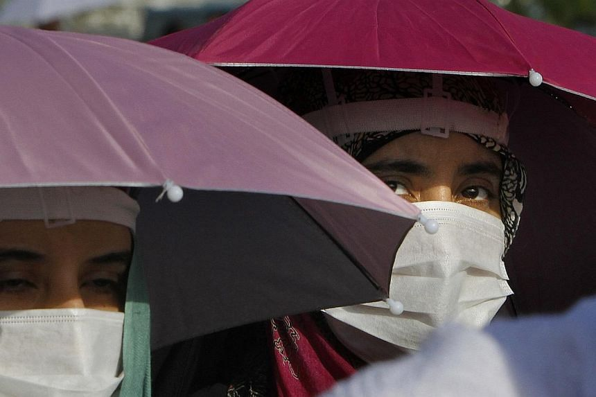 Yemeni Muslim pilgrims wear medical masks as they walk in Arafat, near the holy city of Mecca, Saudi Arabia, on Monday, Oct 14, 2013.Scientists have found cases of Middle East Respiratory Syndrome (Mers) in camels in Qatar, health officials sai
