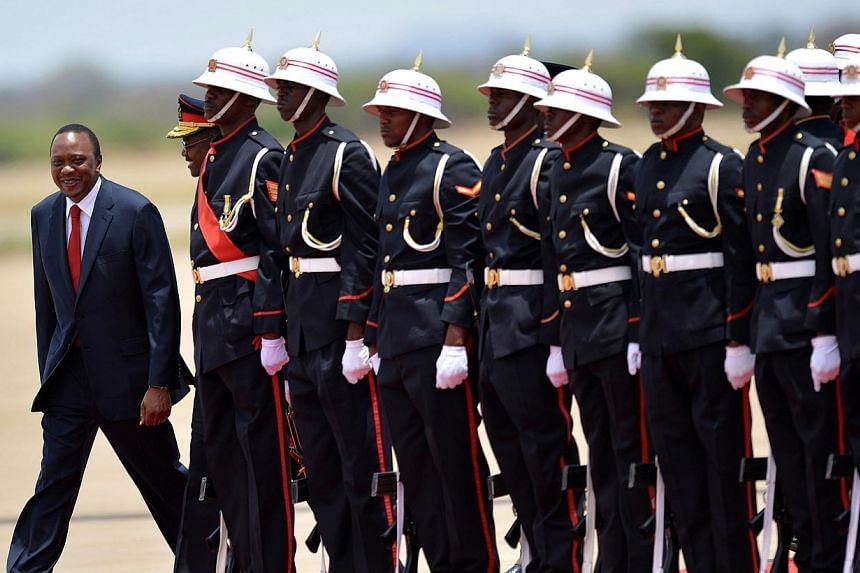 Kenya's President Uhuru Kenyatta (left) inspects a guard of honour mounted by the Botswana Defence Force soldiers for an official visit at the Sir Seretse Khama International airport in Gaborone, on Nov 6, 2013.Kenya launched construction of a