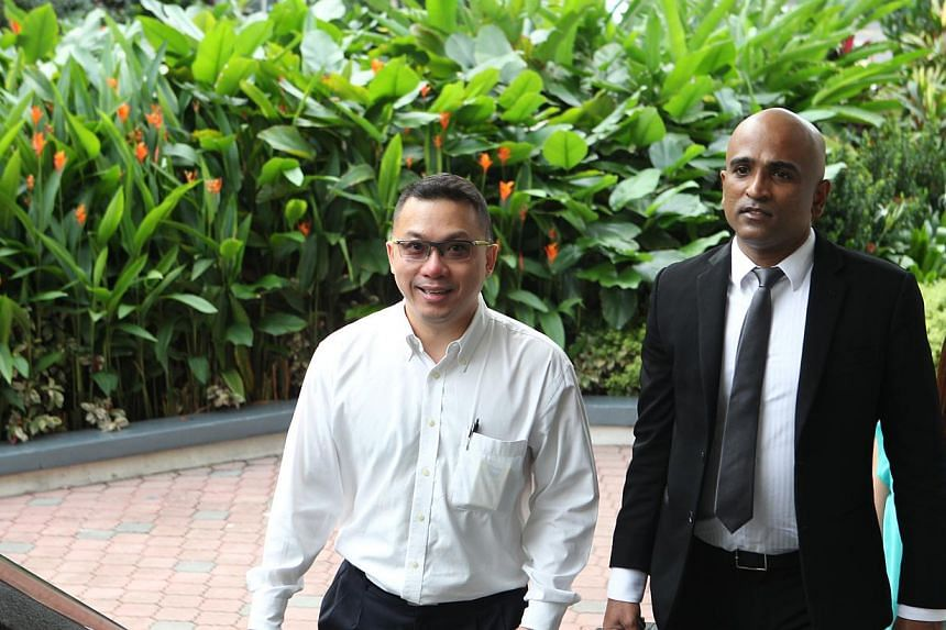 Businessman Delson Moo and lawyer M. Ravi arrive at court on Friday, Nov 29, 2013. Moo was charged in court on Friday with two counts of unauthorised modification of computer material under the Computer Misuse and Cybersecurity Act. -- ST PHOTO: LAU