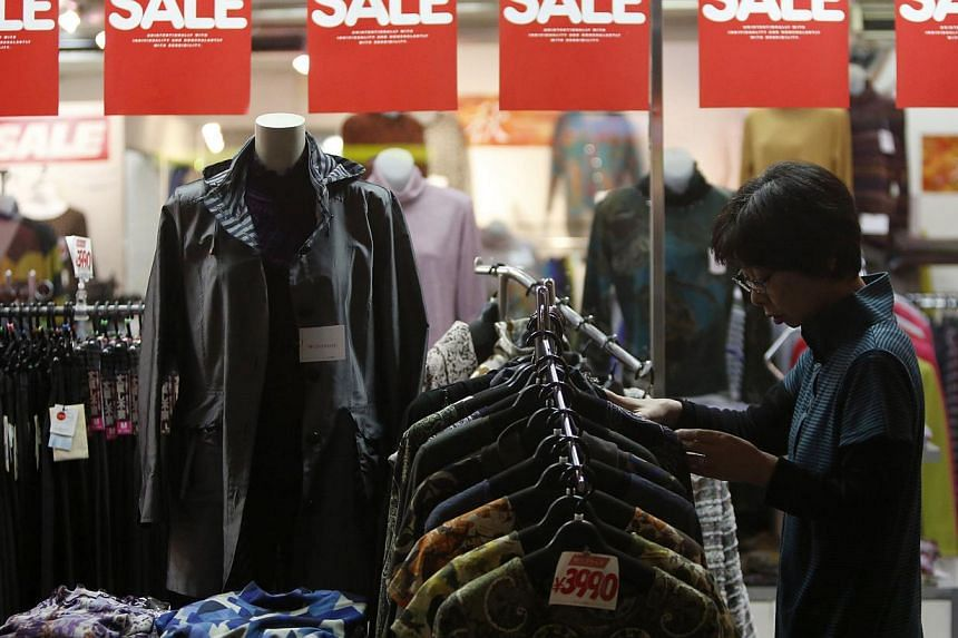 A woman looks at items in a clothing store at a shopping district in Tokyo on Oct 24, 2013. Japanese consumer inflation accelerated to a five-year high and factory output rose for a second straight month in Oct, more evidence a recovery in the world'