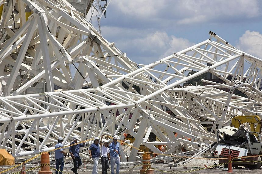 Civil defence and policemen inspect the damage of an accident at the Arena Corinthians, known locally as the Itaquerao, that will host the 2014 World Cup in Sao Paulo, Brazil, on Nov 28, 2013. The Sao Paulo stadium will not be removed from the World