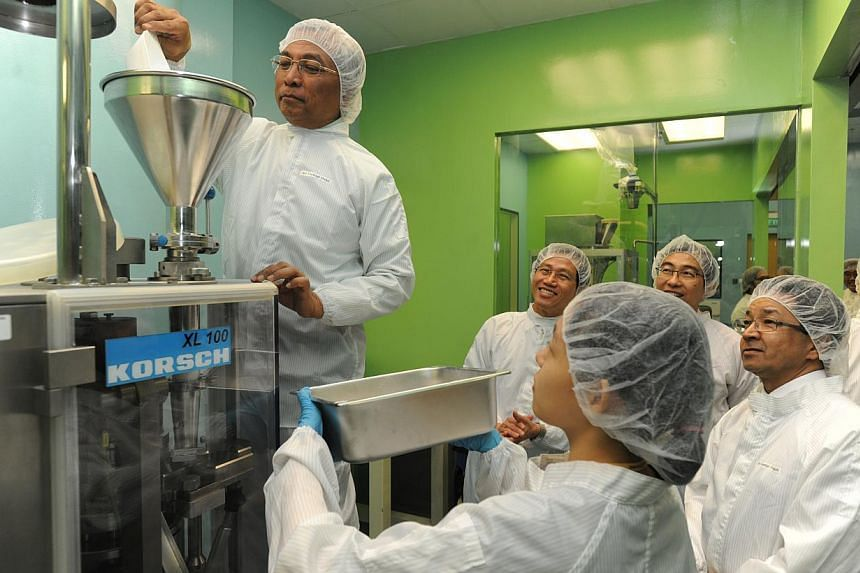 Senior Parliamentary Secretary for Education and Manpower Hawazi Daipi (extreme left) pouring granules into a tablet press to make tablets. With him are (from left) Mr Chan Lee Mun, Nanyang Polytechnic (NYP) principal & CEO; Mr Lim Hock
