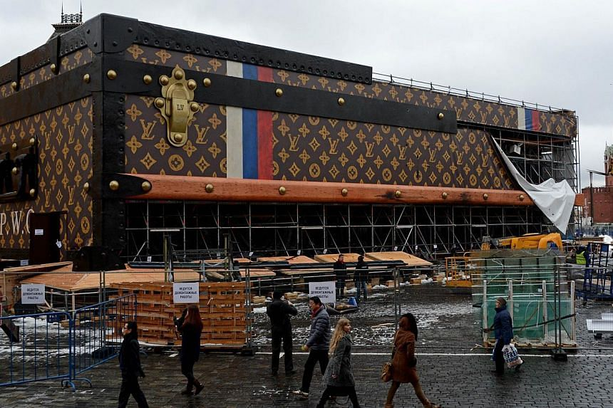 People walk past a giant Louis Vuitton trunk under dismantling on Red Square in Moscow, on Friday, Nov 29, 2013.Workers on Friday began to dismantle a giant Louis Vuitton trunk that triggered an outcry after it was erected on Moscow's iconic Re
