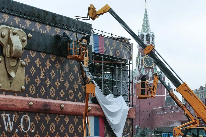 Workers disassemble a Louis Vuitton pavilion shaped like a giant suitcase as Kremlim's Spasskaya Tower is pictured behind in central Moscow on Friday, Nov 29, 2013. -- PHOTO: REUTERS