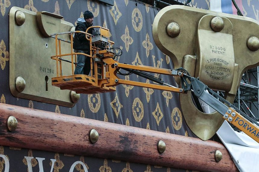 Workers disassemble a Louis Vuitton pavilion shaped like a giant suitcase as Kremlim's Spasskaya Tower is pictured behind in central Moscow on Friday, Nov 29, 2013.-- PHOTO: REUTERS