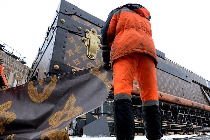 Workers dismantle a giant Louis Vuitton trunk on Red Square in Moscow, on Friday, Nov 29, 2013.-- PHOTO: AFP