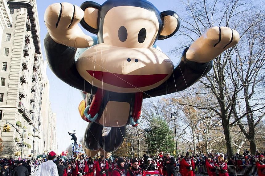 Measuring 12.5m tall, 20m long and 12m wide, Paul Frank's Julius the monkey flies through New York City as one of the largest balloons during the Macy's Thanksgiving Day Parade in New York on Nov 28, 2013. -- PHOTO: AP