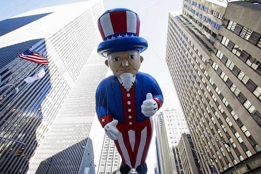 An Uncle Sam balloon floats down Sixth Avenue during the 87th Macy's Thanksgiving Day Parade in New York, on Nov 28, 2013. -- PHOTO: REUTERS