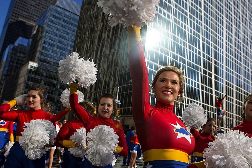 Cheerleaders walk down Sixth Avenue during the 87th Macy's Thanksgiving Day Parade in New York, on Nov 28, 2013. -- PHOTO: REUTERS