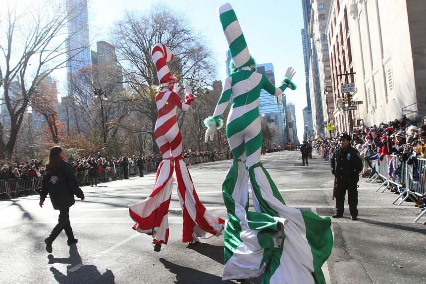 Parade participants dressed as candy canes wave to the crowd as they make their way down New York's Central Park West during the Macy's Thanksgiving Day Parade on Nov 28, 2013. -- PHOTO: AP