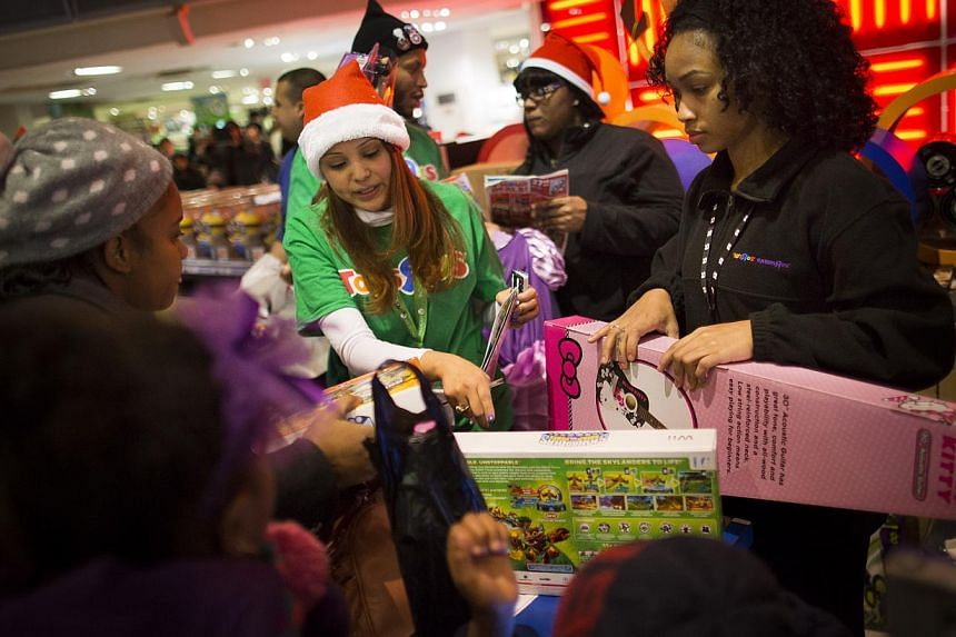 Employees assist customers with their purchases at the Times Square Toys 'R' Us in New York on Nov 28, 2013. Instead of waiting for Black Friday, which is typically the year's biggest shopping day, more than a dozen major retailers are opening on Tha