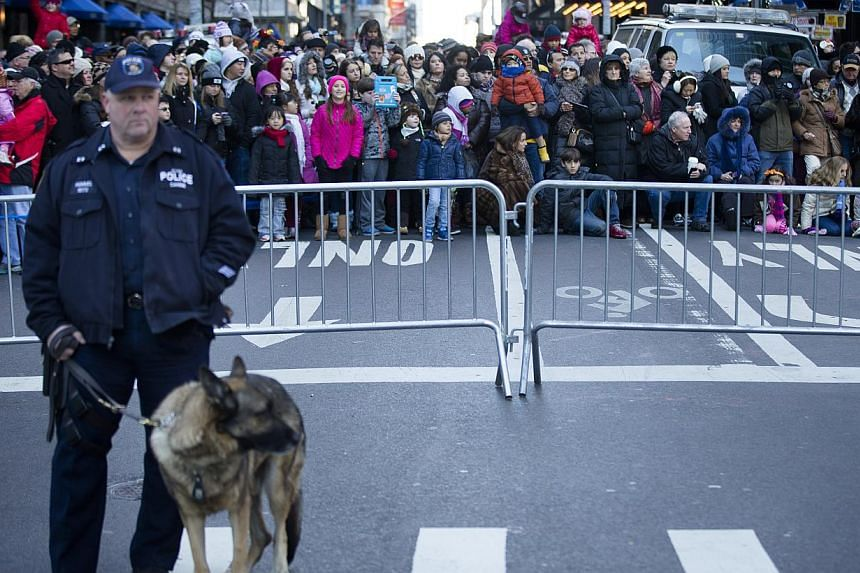 A police officer stands on 6th Avenue as spectators wait behind a barricade during the 87th Annual Macy's Thanksgiving Day Parade in New York on Nov 28, 2013. -- PHOTO: AP