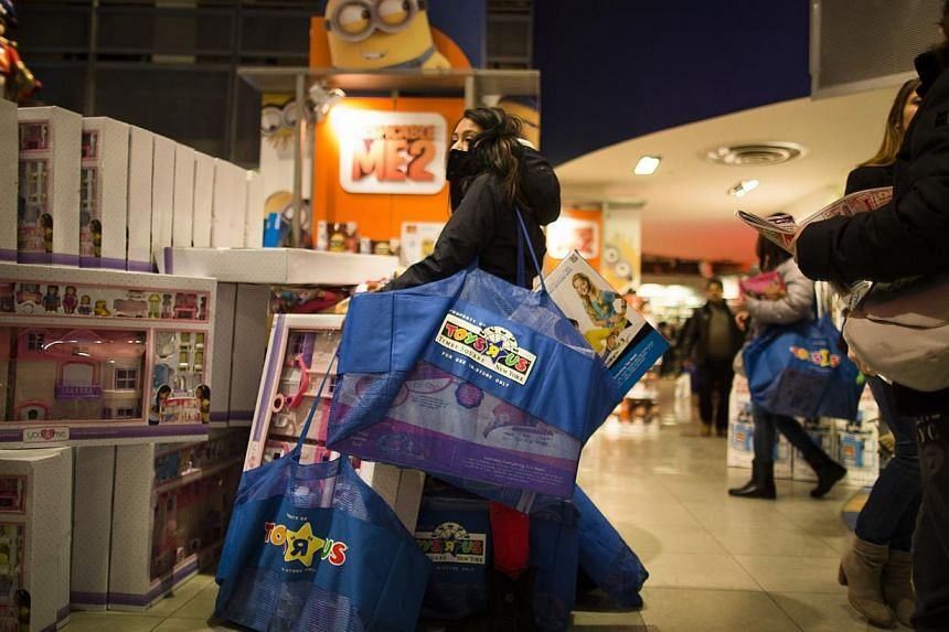 A shopper waits with her bags in the Times Square Toys 'R' Us on Nov 28, 2013, in New York. Instead of waiting for Black Friday, which is typically the year's biggest shopping day, more than a dozen major retailers are opening on Thanksgiving this ye
