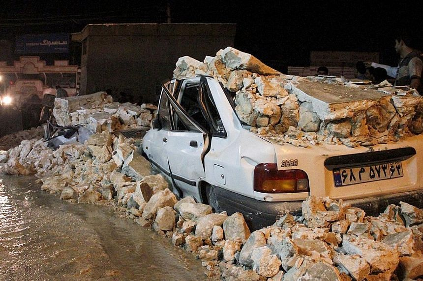 A picture obtained from Iran's ISNA news agency shows the wreckage of a car amid rubble in the Iranian western city of Borazjan, on Nov 28, 2013, after a 5.7 magnitude earthquake struck the country.The earthquake killed eight people and injured
