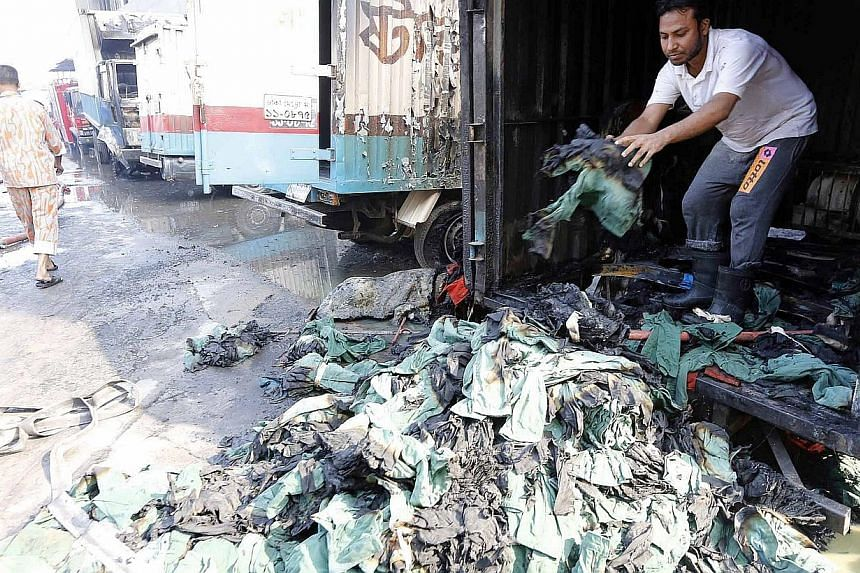 An employee unloading piles of damaged clothes from a van, which was set on fire by protesting workers, at a garment factory in Gazipur, on Nov 29, 2013. A Reuters photographer at the scene said burnt garments strewn on the floors bore brand names fr