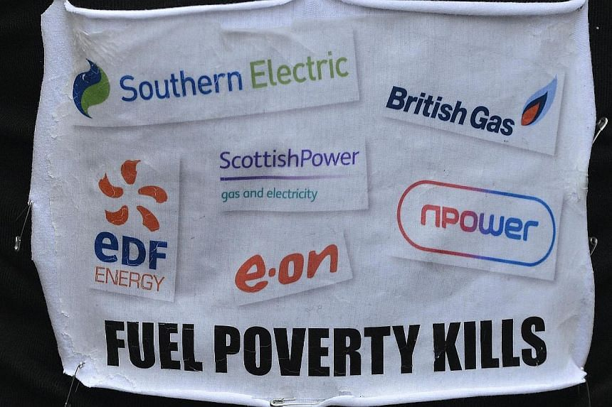 A demonstrator wears a message during a march to the headquarters of energy company npower during a protest against energy prices, London, on Nov 26, 2013. The government has asked Britain's six biggest energy suppliers to freeze prices for gas and e