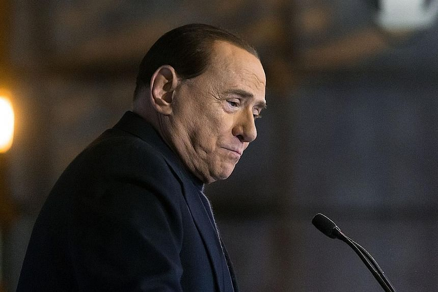 Silvio Berlusconi pauses as he addresses his supporters during a rally in Rome, on Wednesday, Nov 27, 2013. An Italian court accused former Prime Minister Silvio Berlusconi, on Friday, Nov 29, 2013, of bribing witnesses to give false testimony in a t