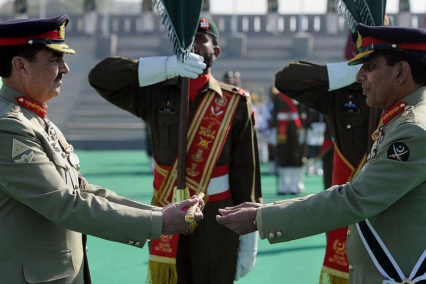 Pakistan's new army chief General Raheel Sharif (left) receives the change of command baton from outgoing army chief General Ashfaq Kayani (right) during the change of command ceremony in Rawalpindi, on Nov 29, 2013.Gen Sharif now holds the mos