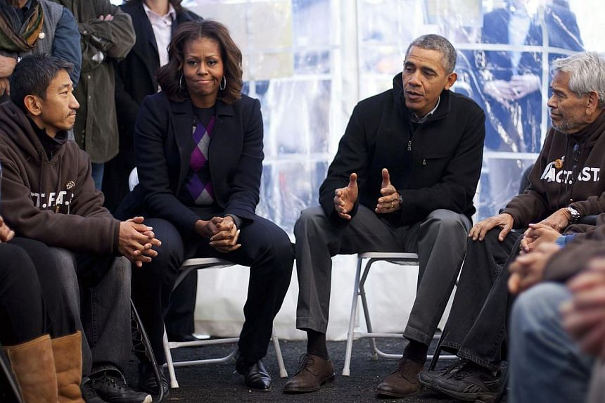 President Barack Obama and First Lady Michelle Obama visit with individuals who are taking part in Fast for Families on the National Mall in Washington, Friday, Nov 29, 2013. Seated nearest Mr Obama are Dae Joong Yoon (left) and Eliseo Medina (right)