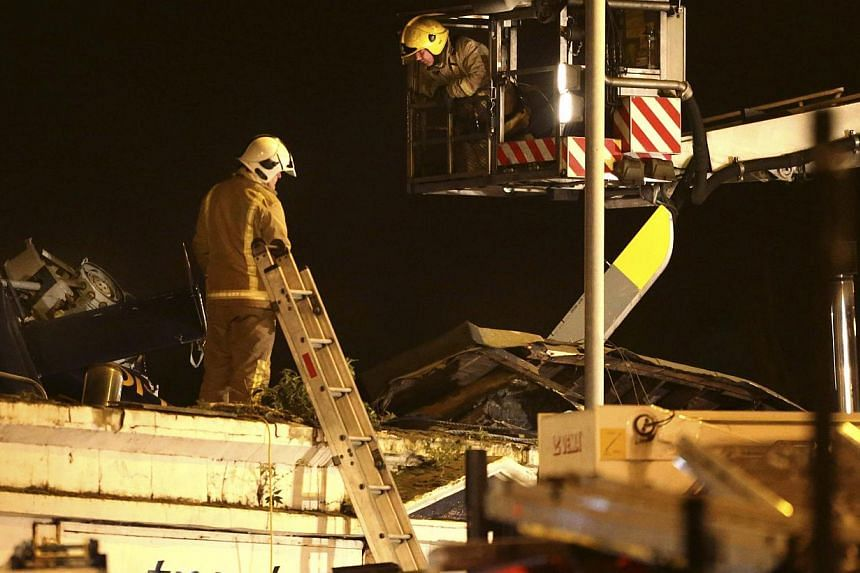 Firefighters inspect the damage at the site of a helicopter crash, in Glasgow early on Saturday, Nov 30, 2013. The police helicopter crashed late on Friday night into the roof of a popular pub in Glasgow, Scotland, leaving the building littered with
