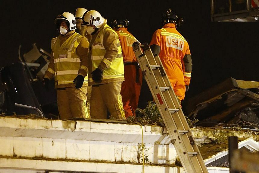 Rescue workers examine the wreckage of a police helicopter which crashed onto the roof of the Clutha Vaults pub in Glasgow, Scotland on Nov 30, 2013. -- PHOTO: REUTERS