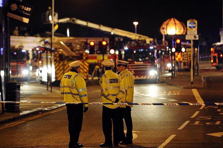 Emergency services gather at the site where a police helicopter crashed into a pub in central Glasgow, Scotland, shortly after midnight on Nov 30, 2013. The police helicopter crashed into the Clutha pub and fatalities are likely, Scotland's First Min